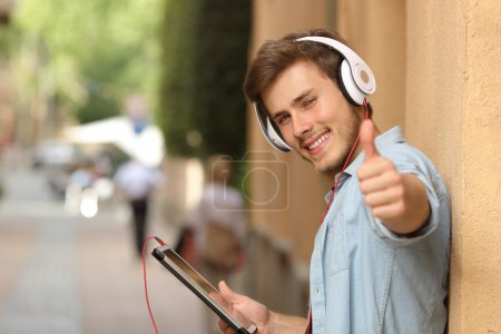 Man using a tablet with thumbs up in the street
