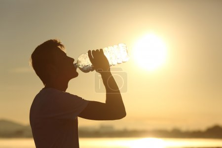 Fitness man silhouette drinking water from a bottle