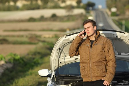 Photo for Guy calling roadside assistance for his breakdown car i a country road - Royalty Free Image