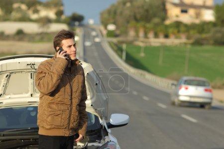 Photo pour Heureux homme réclame l'assistance routière de sa voiture de panne sur une route de campagne - image libre de droit