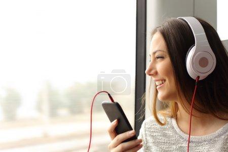 Photo pour Heureux adolescent passager écoutant la musique voyageant dans un train et regardant par la fenêtre - image libre de droit