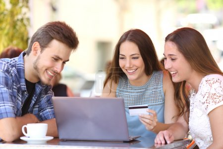 Friends shopping online with a credit card and a laptop