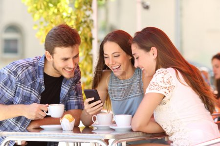 Photo for Three happy friends watching social media in a smart phone in a coffee shop - Royalty Free Image