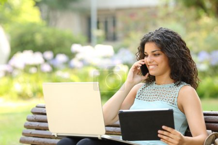 Photo for Entrepreneur working with multiple devices sitting in a bench in a park - Royalty Free Image
