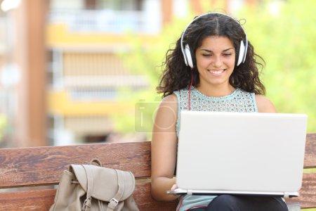 Photo pour Freelance travaillant avec un ordinateur portable et écouteurs assis sur un banc dans un parc - image libre de droit