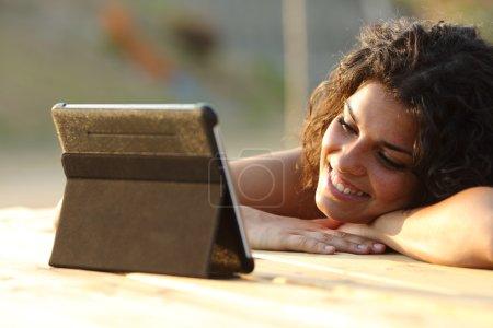 Photo pour Gros plan d'une femme, regarder des vidéos sur un comprimé le soir au coucher du soleil dans un tableau de parc - image libre de droit