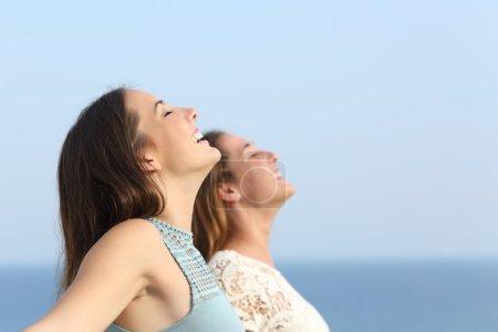 Two girls breathing deep fresh air on the beach