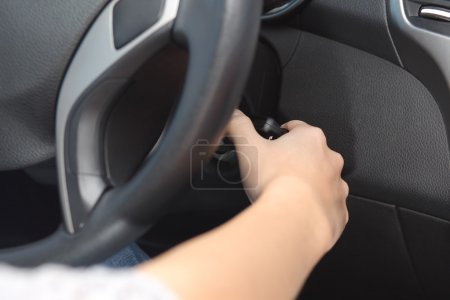 Driver hand starting the car with the key