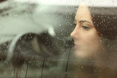 Photo for Sad woman or teenager girl looking through a steamy car window - Royalty Free Image