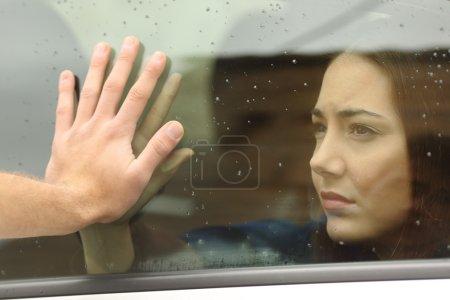 Photo pour Couple dire au revoir avant voyage voiture main dans la main à travers la fenêtre - image libre de droit