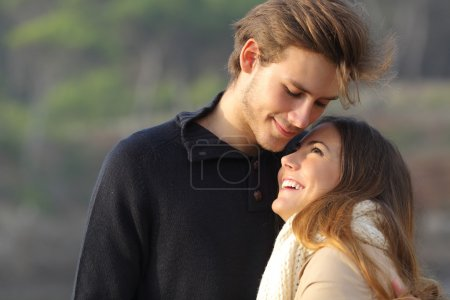 Foto de Pareja feliz abrazando en el amor al aire libre al atardecer con un fondo desenfocado - Imagen libre de derechos