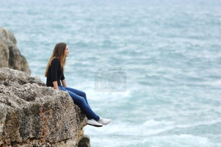 Photo for Side view of a full body of a casual woman thinking sitting in a cliff watching the sea - Royalty Free Image