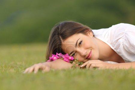 Photo pour Femme décontractée, reposant sur l'herbe verte avec des fleurs dans un parc avec fond vert - image libre de droit