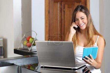 Photo pour Femme entrepreneur multi-tâches travailler avec une tablette pour ordinateur portable et un téléphone dans la cuisine à la maison - image libre de droit