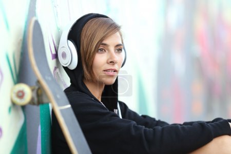 Young skater girl listening to the music with headphones