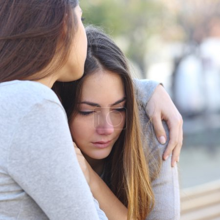 Sad girl crying and a friend comforting her