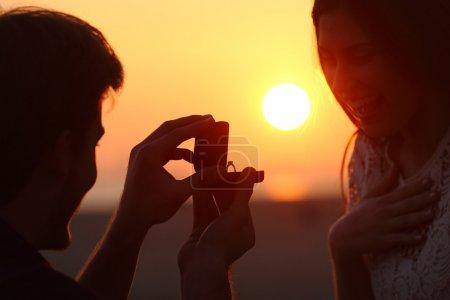 Rétro-éclairage d'une proposition de mariage au coucher du soleil