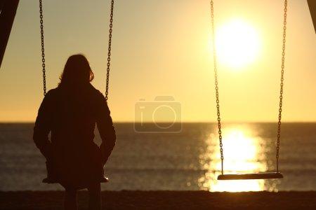 Photo pour Femme solitaire regardant le coucher du soleil seul en hiver sur la plage au coucher du soleil - image libre de droit
