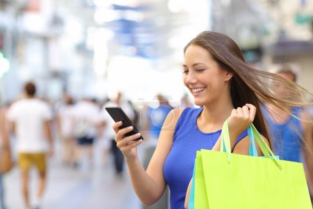 Shopper shopping with smartphone in the street