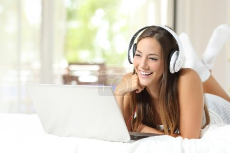 Girl with headphones reading in a laptop at home