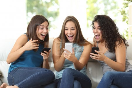 Three friends amazed watching a smart phone