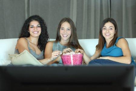 Three happy friends watching tv