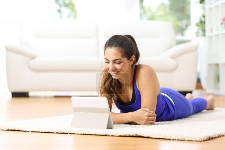 Sportswoman watching sport videos in a tablet