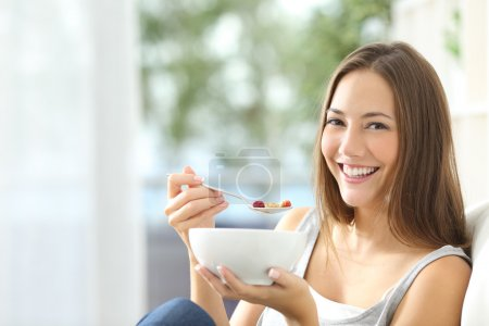 Photo for Casual happy woman dieting and eating cornflakes sitting on a couch at home - Royalty Free Image