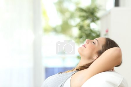 Profile of a beautiful woman relaxing lying on a c...