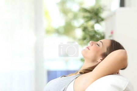 Foto de Perfil de una hermosa mujer tendida en un sofá en casa de relajación - Imagen libre de derechos