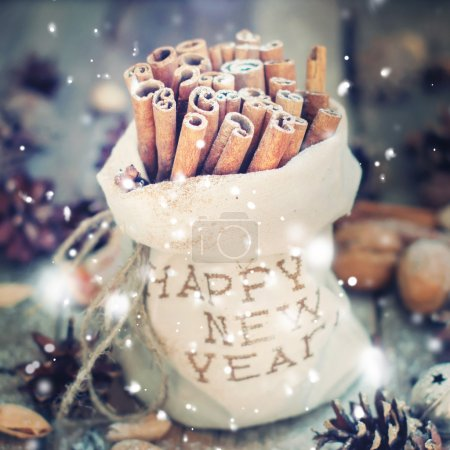 Photo pour Linen Bag with Embroidery Happy New Year with Sticks of Cinnamon and  other Christmas Ingredients, Pine cones, Walnuts on Wooden Background. Toned in Yellow-Blue Vintage Colors with snow effects - image libre de droit