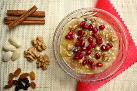 Photo for Ashure or Noah's pudding, the turkish dessert porridge in glass bowl on natural matting - Royalty Free Image