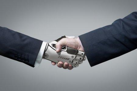 Photo pour Mains d'homme et de robot d'affaires dans la poignée de main. Concept de conception de technologie d'intelligence artificielle - image libre de droit