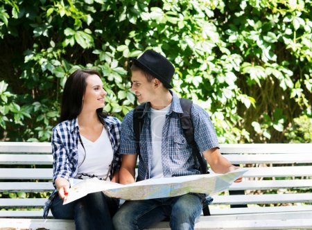 Photo for Young traveling couple checking out the map in the park. - Royalty Free Image