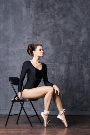 Young ballerina sitting on a chair in a point shoes