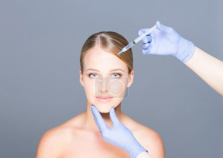 Doctor injecting botox in a beautiful face of a young woman