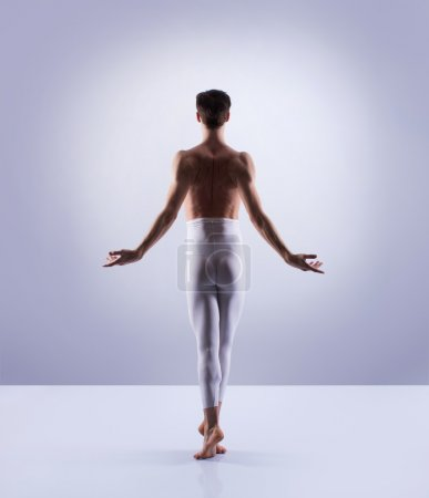 Athletic ballet dancer performing in a studio