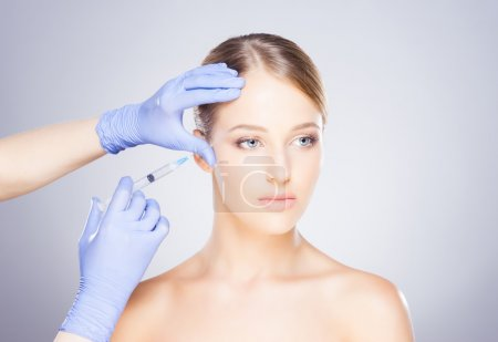 Doctor injecting botox into a woman's face
