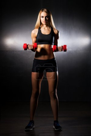 Sporty girl training with dumbbells