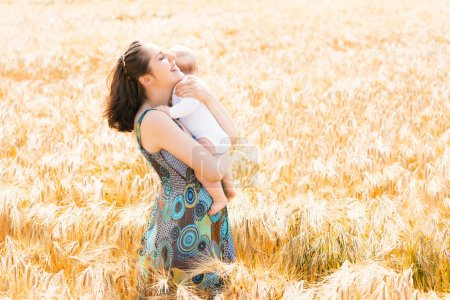 Woman with her infant baby in a field