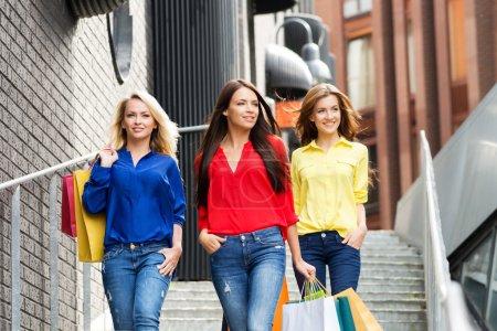 Photo pour Groupe de belles filles confiantes descendant les escaliers extérieurs avec des sacs à provisions . - image libre de droit