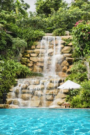 Luxury swimming pool nearby tropical forest and waterfall