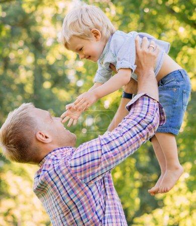 Photo pour Jeune papa passe du temps avec son fils dans le parc à la journée ensoleillée d'été - image libre de droit