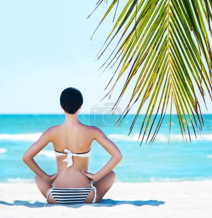 Photo for Back of a beautiful and thin female meditating on the beach over background with ocean and palm. - Royalty Free Image