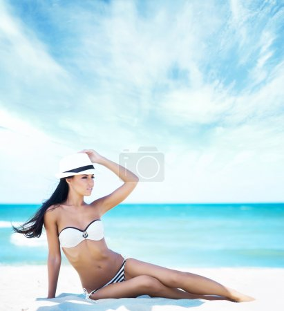 Woman in sexy swimwear wearing a hat and tanning on the beach