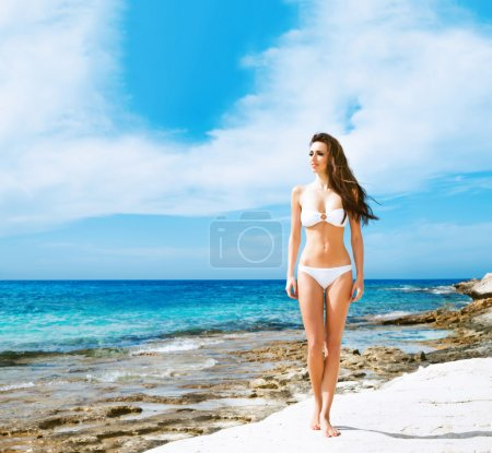 Young and sexy woman in a white swimsuit on the beach
