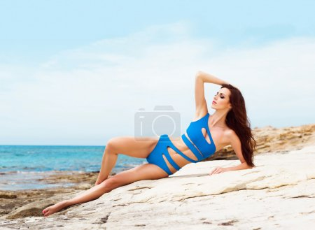 Young and sexy woman in a blue swimsuit on the beach