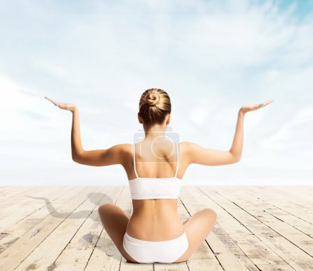 Photo for Beautiful woman with a perfect body meditating on a pier. Yoga, sport and summer concept. - Royalty Free Image