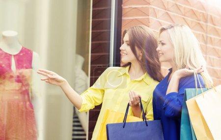 Photo pour Filles attrayantes marchant dans le centre-ville. Des femmes avec des sacs à provisions. Les amis dépensent de l'argent. Remise et concept de shopping . - image libre de droit