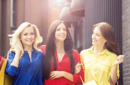 Photo pour Jolies femmes avec des sacs à provisions. Des amis marchent dehors en ville. Escompte, shopping et concept de dépense d'argent . - image libre de droit